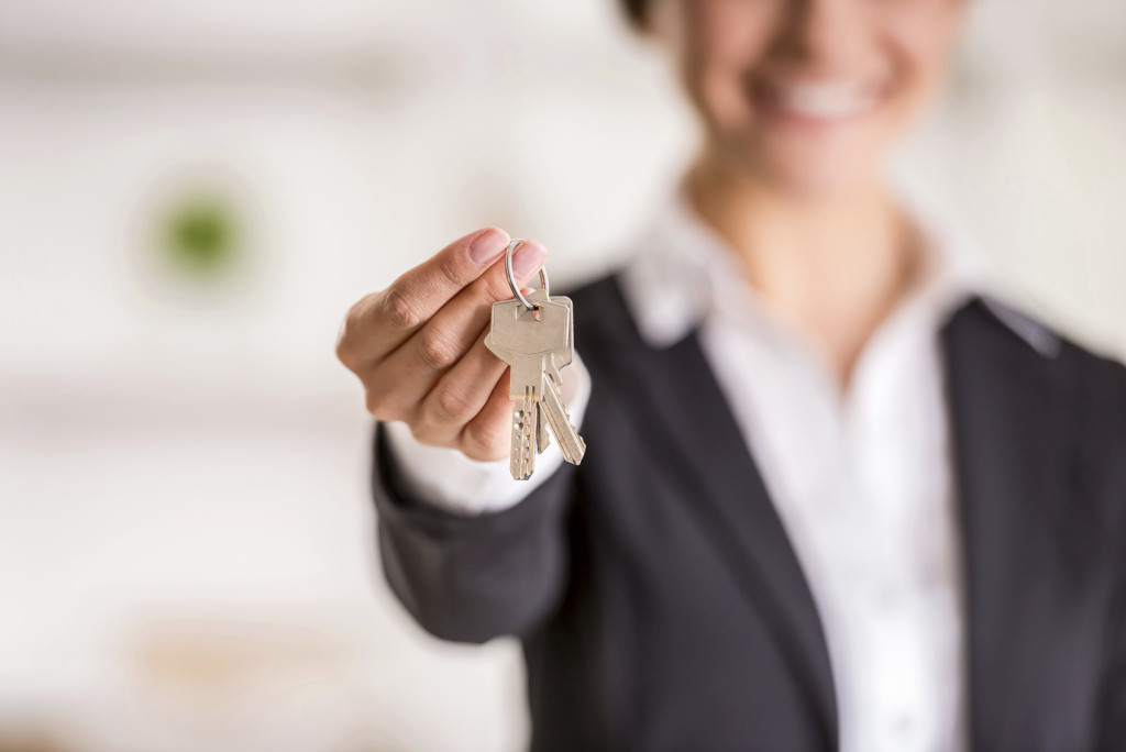 Realtor is giving the keys to an apartment to clients. Focus on the keys.