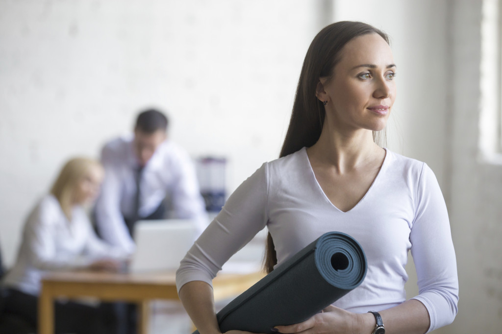 Business and healthy lifestyle concept. Portrait of beautiful sporty young office woman standing with yoga mat at workplace on break time