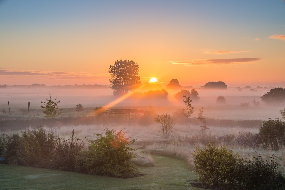A misty English countryside sunrise in September