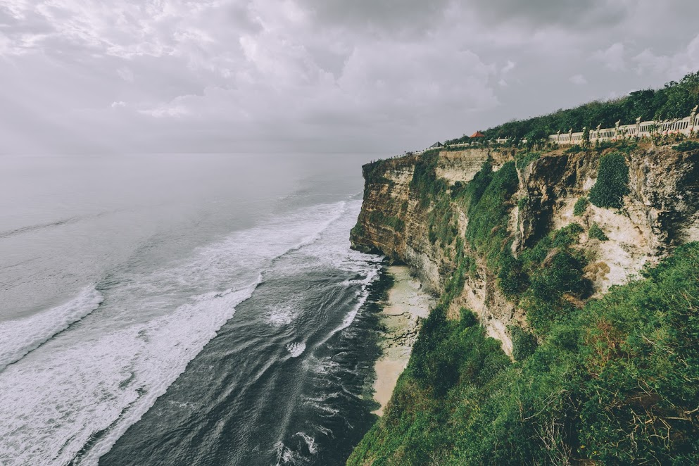 This is a huge cliff in Uluwatu, Bali, you can walk on a path, close to the edge, that brings you to a beautiful temple, Uluwatu Temple. The weather in Bali changes a lot, i got lucky to find this magical atmosphere with this soft light right on the rocks.