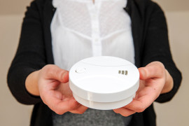 Woman holding white smoke detector - the device that senses smoke, typically as an indicator of fire